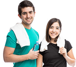 Smiling male and female students with towels after a workout